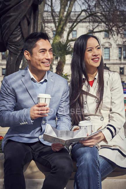 Paar auf der Brüstung sitzen und Kaffee trinken — Stockfoto