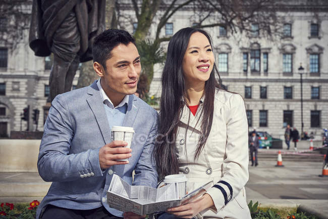 Couple sitting on parapet and drinking coffee — Stock Photo