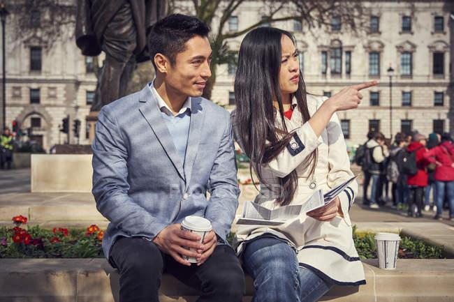 Пара, сидя на парапете и пить кофе — стоковое фото