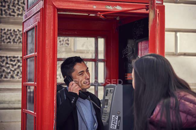 Casal fazer telefonema enquanto passeia — Fotografia de Stock