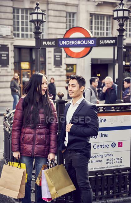 Coppia giapponese che cammina con i sacchetti di shopping — Foto stock