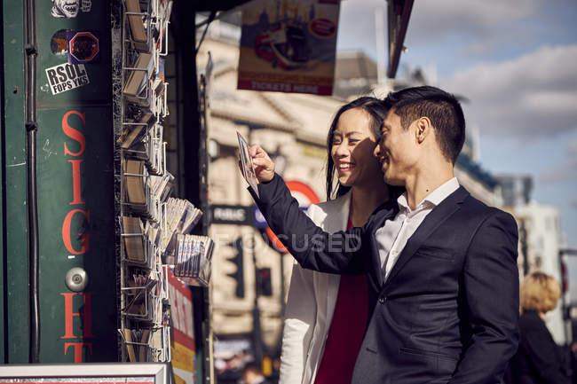 Paar wählt Postkarten im Ständer — Stockfoto