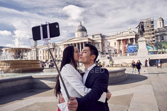 Пара делает селфи у фонтана на Трафальгарской площади — стоковое фото