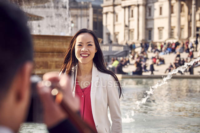 Man photographing girlfriend near fountain — Stock Photo