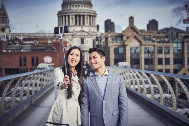 Casal tomando selfie enquanto está em pé na Millennium Bridge — Fotografia de Stock