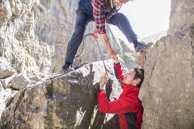 Dos alpinistas ayudando unos a otros - foto de stock