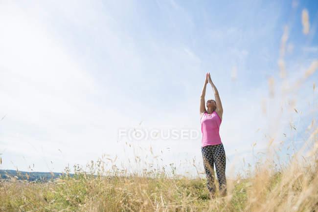 Femme bénéficie d'une journée ensoleillée dans la prairie — Photo de stock