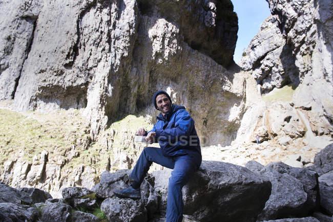 Montañero sentado comiendo - foto de stock