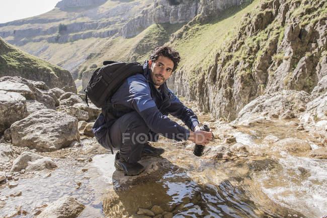 Alpinista su botella de agua de relleno - foto de stock