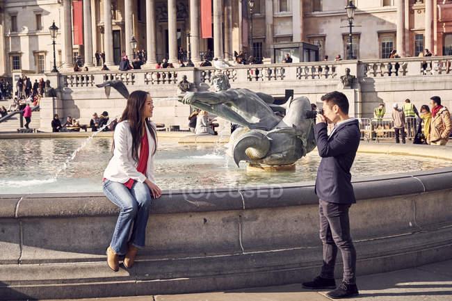 Жінка на possing краю фонтан для камери — стокове фото