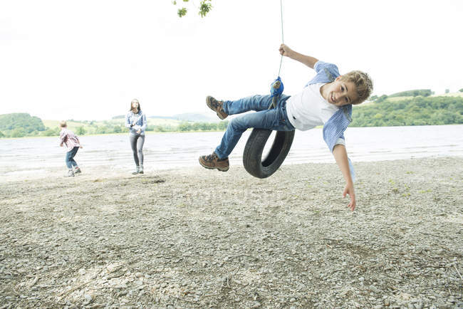 Woman and two boys playing on tire — Stock Photo