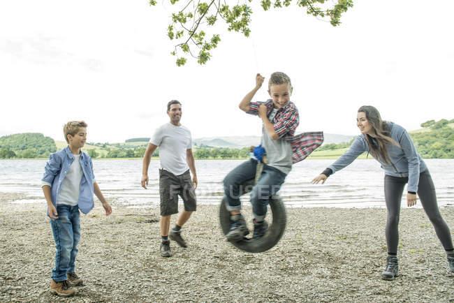 Familie spielt auf Reifen, der an Baum hängt — Stockfoto