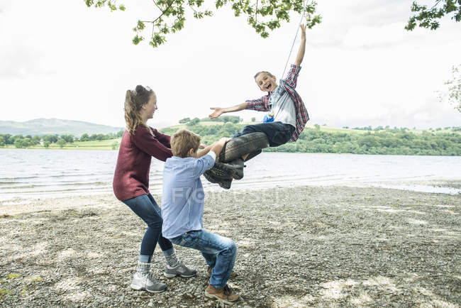Girl and boys playing on tire hanging from tree — Stock Photo