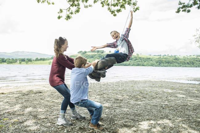Mädchen und Jungen spielen auf Reifen, die an Baum hängen — Stockfoto