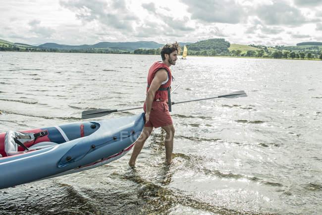 Mann schleppt eine Kajak ins Wasser — Stockfoto