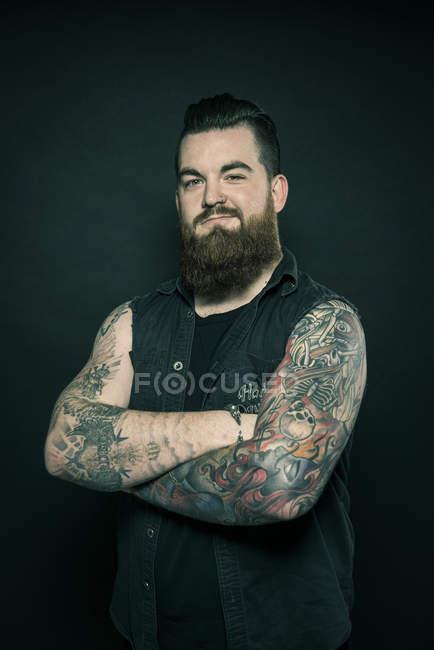 Человек со сложенными татуированными руками — стоковое фото