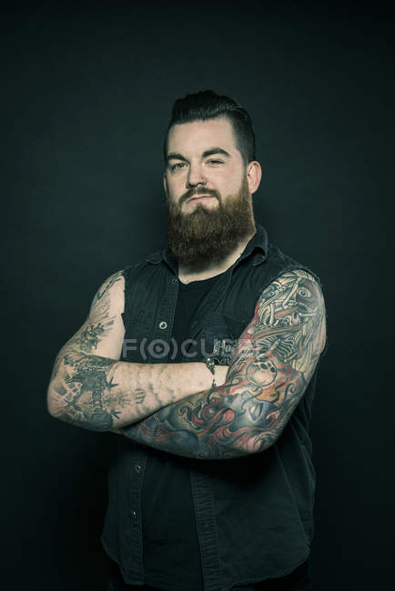 Man with folded tattooed arms — Stock Photo
