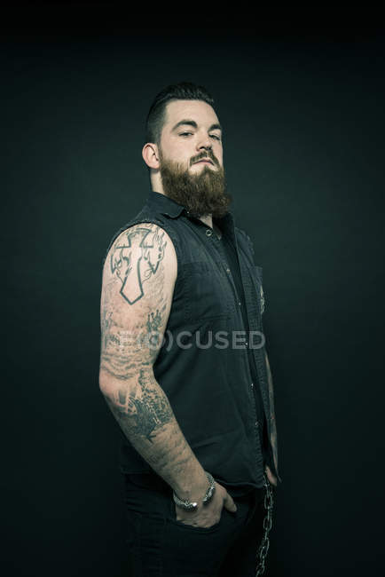 Man with tattooed arms in pockets — Stock Photo