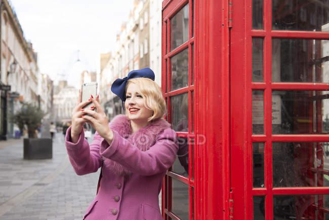 Mujer tomando selfie fuera un quiosco del teléfono - foto de stock