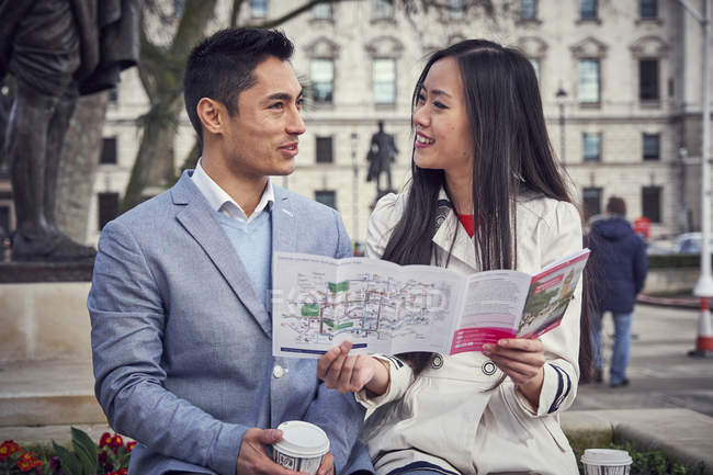 Couple sitting outside holding city guide — Stock Photo