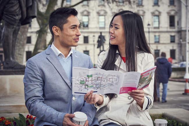 Paar, draußen halten Stadtführer — Stockfoto