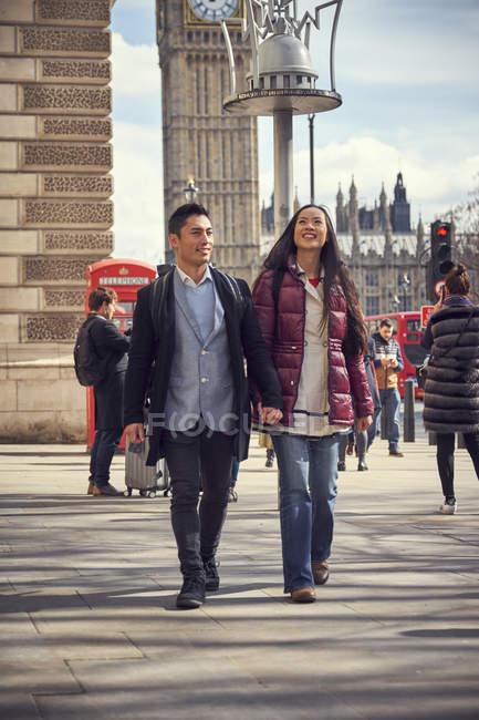 Молодая пара, идущая по Лондонской улице — стоковое фото
