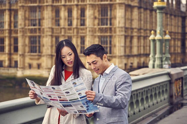 Couple pondering over city guide — Stock Photo