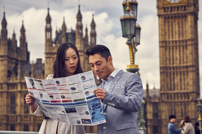 Couple looking into city guide — Stock Photo