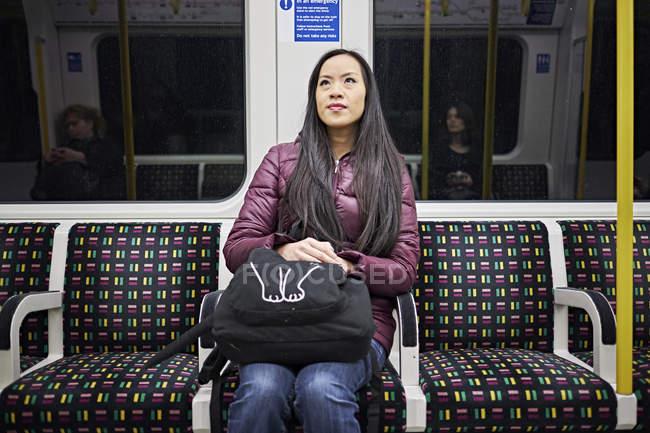 Donna che cavalca su treno tubo — Foto stock