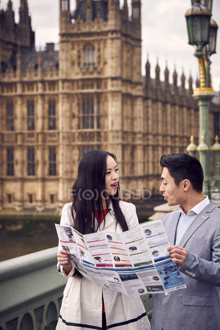 Couple discussing over city guide on bridge — Stock Photo