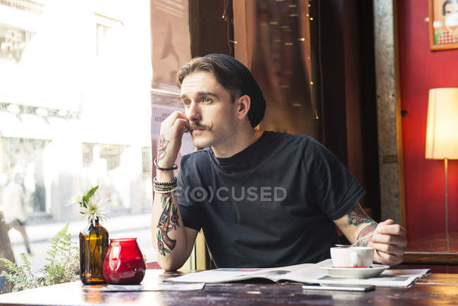 Man sitting at table and looking at window — Stock Photo