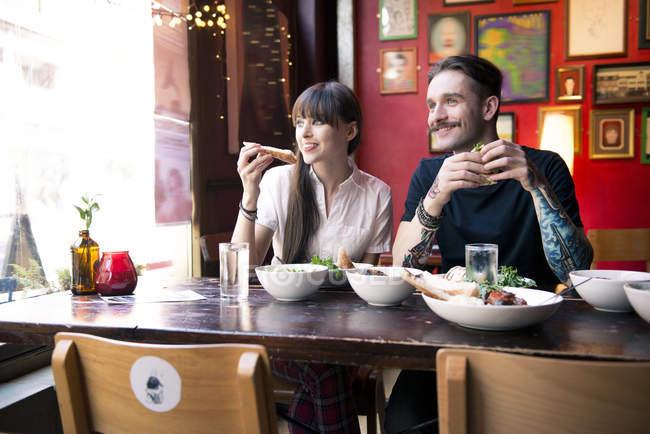 Couple enjoying meal in coffee shop — Stock Photo
