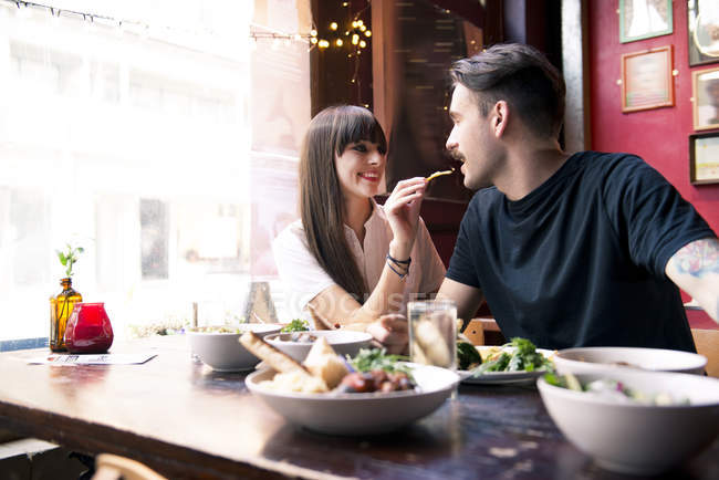 Couple enjoying meal in coffee shop — Stock Photo