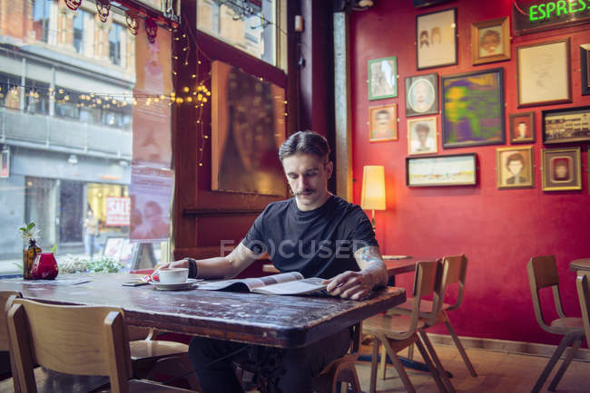 Man sitting at table and reading magazine — Stock Photo