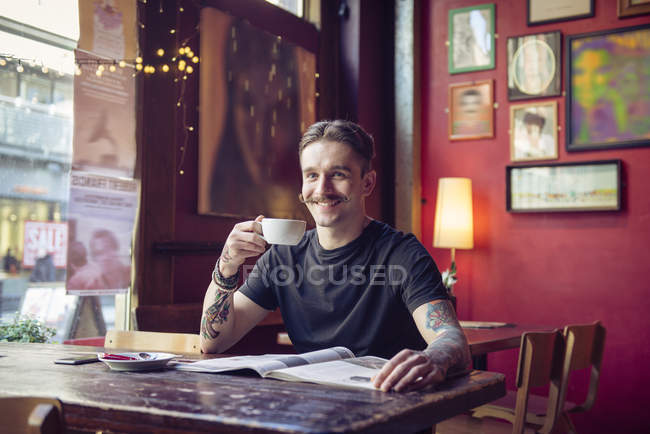 Man sitting at table with cup of tea — Stock Photo