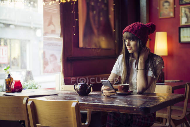 Woman sitting at table and looking at window — Stock Photo