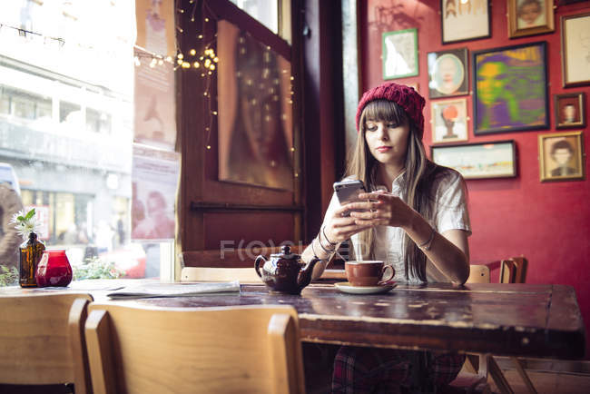 Woman sitting at table and using smartphone — Stock Photo