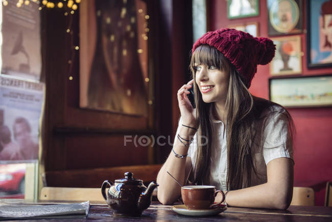 Woman sitting at table and talking on phone — Stock Photo