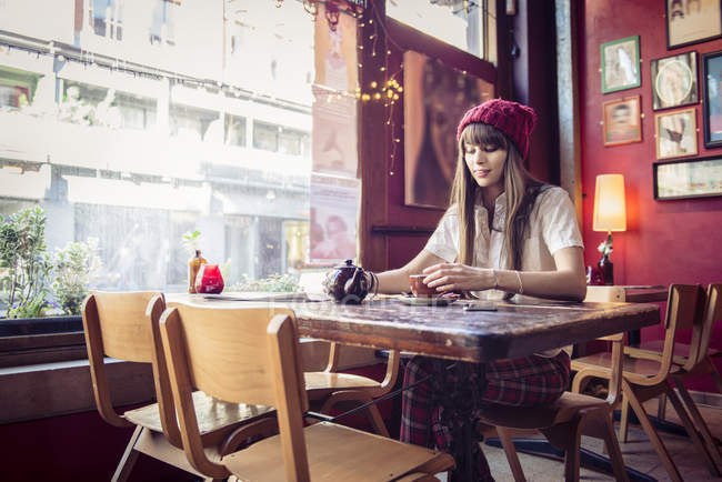 Woman sitting at table in coffee shop — Stock Photo