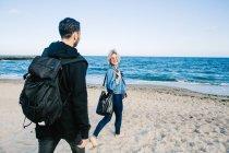 Pareja caminando en la orilla del mar - foto de stock