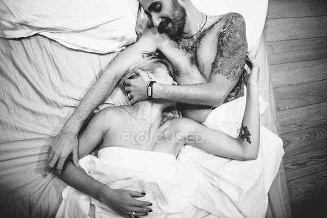 Tendre couple embrassant au lit — Photo de stock