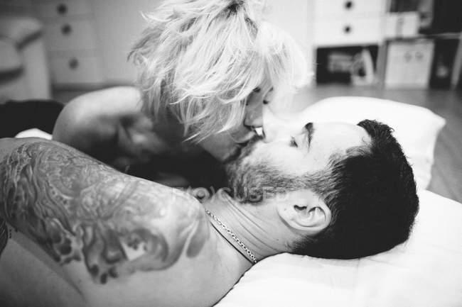 Couple embrasser dans le lit — Photo de stock