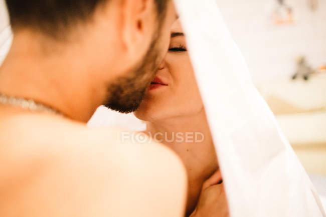 Couple kissing in bed - foto de stock