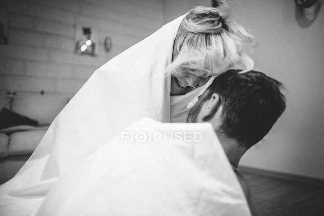 Par abrazar en la cama - foto de stock