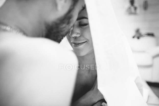 Пара обнимается в постели — стоковое фото