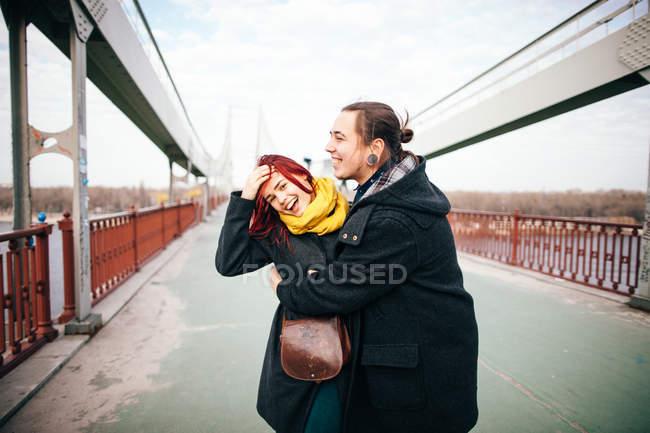 Pareja caminando en puente - foto de stock
