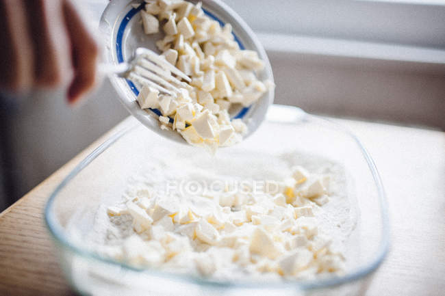 Hand putting butter to baking tray — Stock Photo