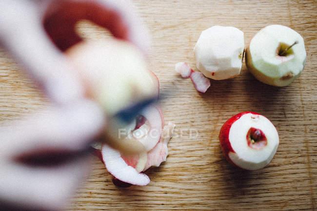 Human hands skinning apples — Stock Photo
