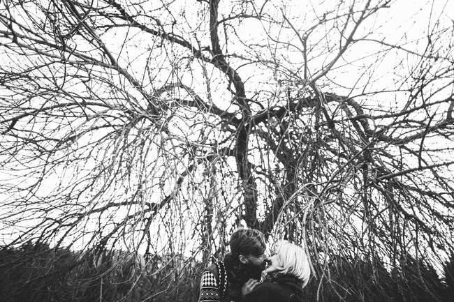 Seitenansicht des jungen Paares umarmen und küssen im freien — Stockfoto