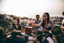 Amis, s'amuser avec soufflant des bulles — Photo de stock